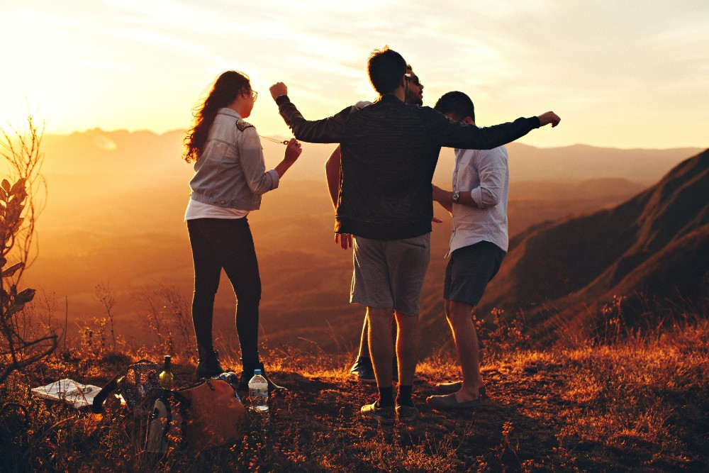 four-person-standing-at-top-of-grassy-mountain-697244-1