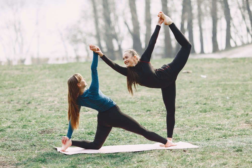 young-women-practicing-acro-yoga-in-park-4127293-1